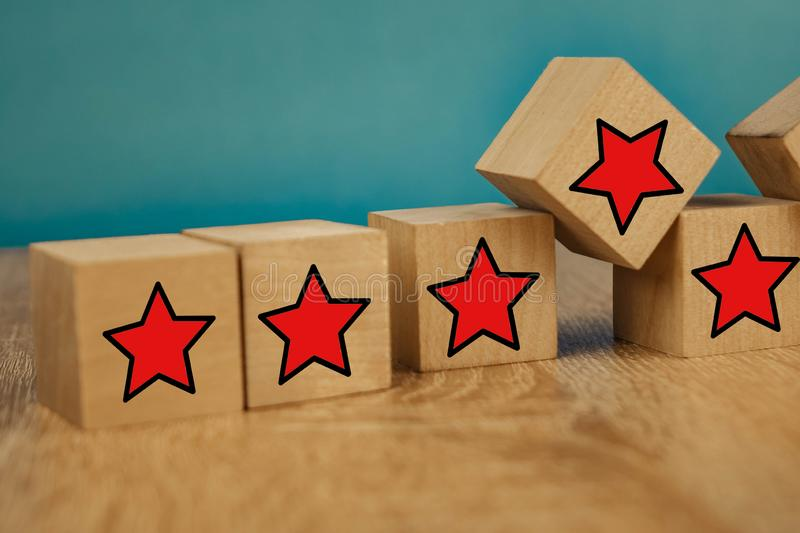 Red stars on wooden cubes on a blue background. Stars mean assessing quality. five-point rating system. 5, best, business, customer, evaluation, excellent royalty free stock image
