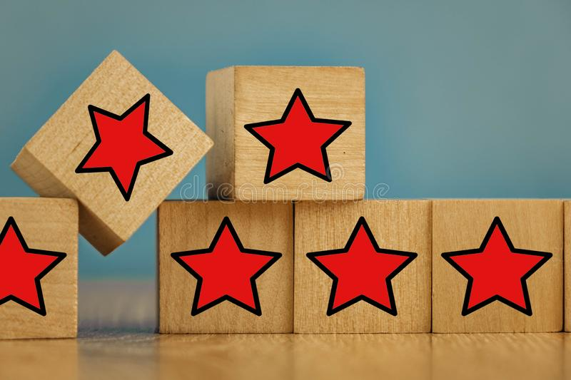 Red stars on wooden cubes on a blue background. Stars mean assessing quality. five-point rating system. 5, best, business, customer, evaluation, excellent royalty free stock photos