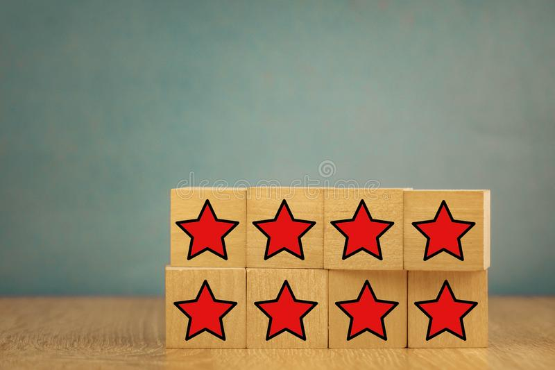 Red stars on wooden cubes on a blue background. Stars mean assessing quality. five-point rating system. 5, best, business, customer, evaluation, excellent royalty free stock images