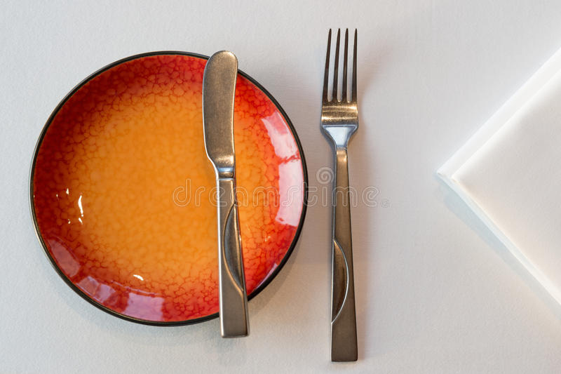 Red starter meal setup. Starter meal setup with red hot plate and white napkin decoration. Selective focus stock photography