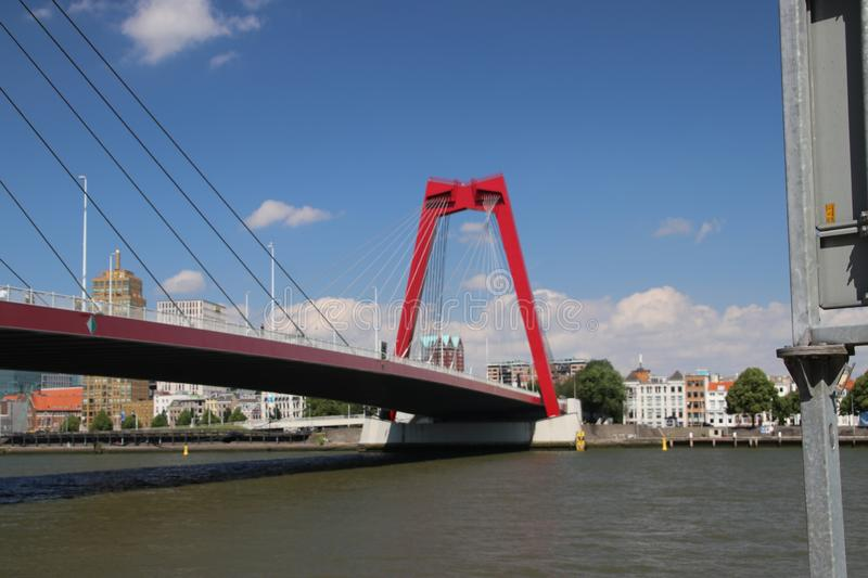 Red steel suspension bridge named Willemsbrug in the city center of Rotterdam over river Nieuwe Maas in the Netherlands royalty free stock images