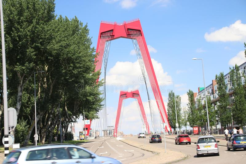 Red steel suspension bridge named Willemsbrug in the city center of Rotterdam over river Nieuwe Maas in the Netherlands royalty free stock photo