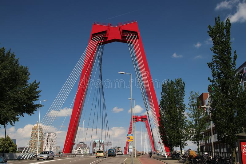 Red steel suspension bridge named Willemsbrug in the city center of Rotterdam over river Nieuwe Maas in the Netherlands royalty free stock image