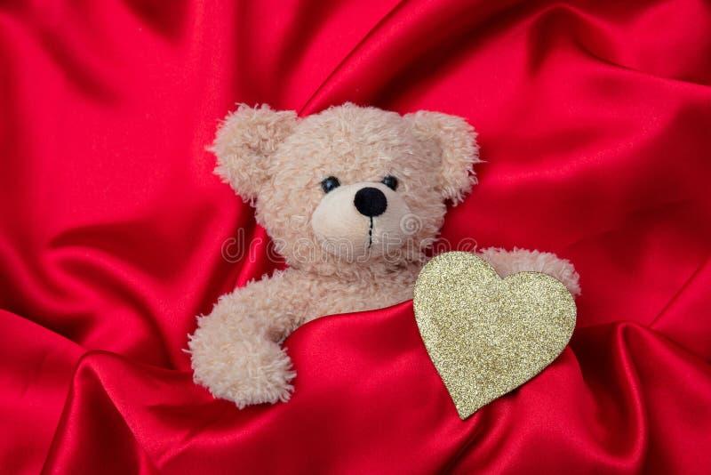 red steg Bästa sikt av en nallebjörn och en guld- hjärta, på röd siden- bakgrund royaltyfri foto