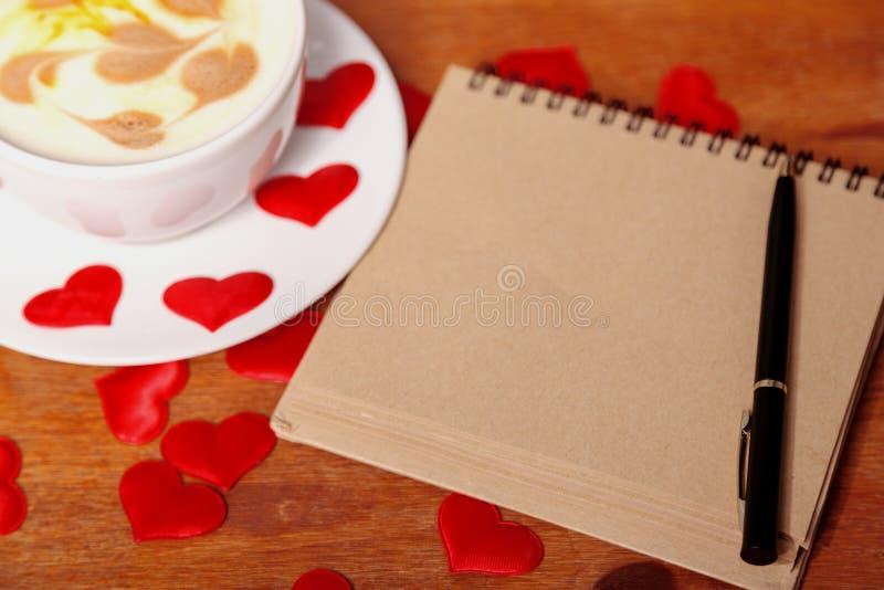 red steg Cappuccinokopp med en lattekonst i form av hjärtor, en gammal pappers- anteckningsbok och en penna på en trätabell royaltyfria bilder