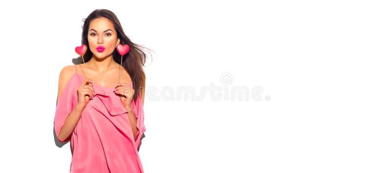 red steg För modemodellen för skönhet formade den glade unga flickan med Valentine Heart kakor i hennes händer arkivbild