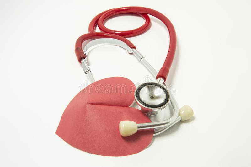 Red stethoscope chestpiece lying to red heart shape on white background vertically isolated. The idea or concept for cardiology -. Treatment and diagnosis of royalty free stock photography