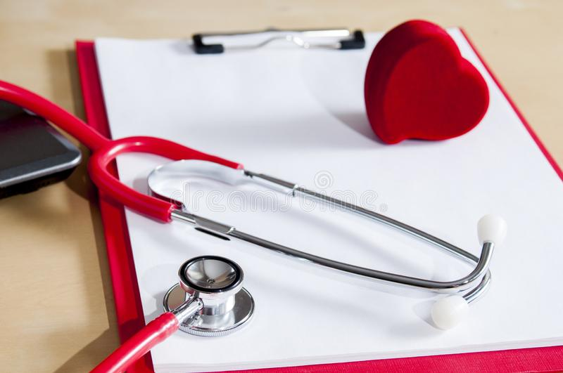 Red stethoscope and heart on a red clipboard. Near laptop. Medical device. Treatment, health care. Heart examination. Studying the. Pulse doctor equipment stock image