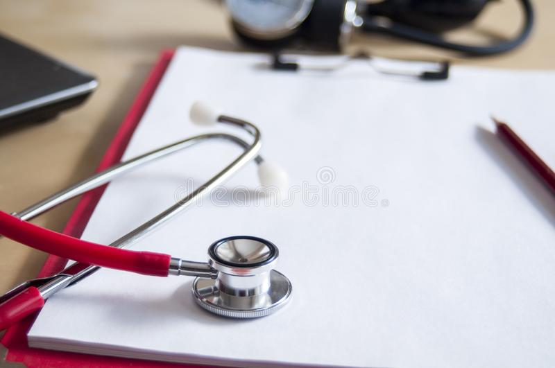 Red stethoscope and red pencil on a red clipboard. Near laptop and tonometer. Copy space. Medical device. Treatment, health care. Heart examination. Studying stock images
