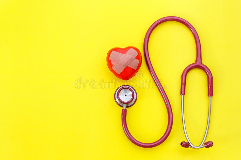 Red stethoscope and red heart shape on yellow background. For ch stock photos