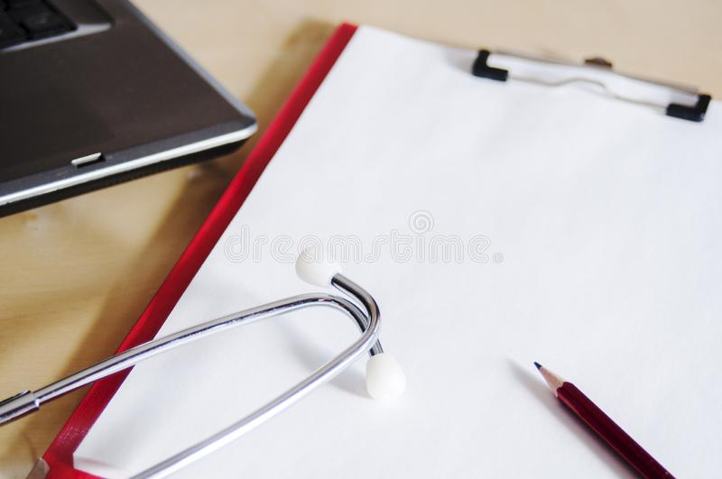 Red stethoscope and red pencil on a red clipboard. Near laptop. Medical device. Treatment, health care. Heart examination. Studying the pulse doctor equipment royalty free stock image