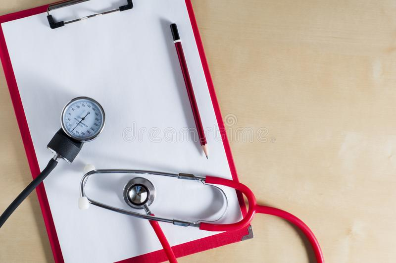 Red stethoscope, tonometer and red pencil on a red clipboard. Top view. Right copy space. Medical device. Treatment, health care. Heart examination. Studying stock photos
