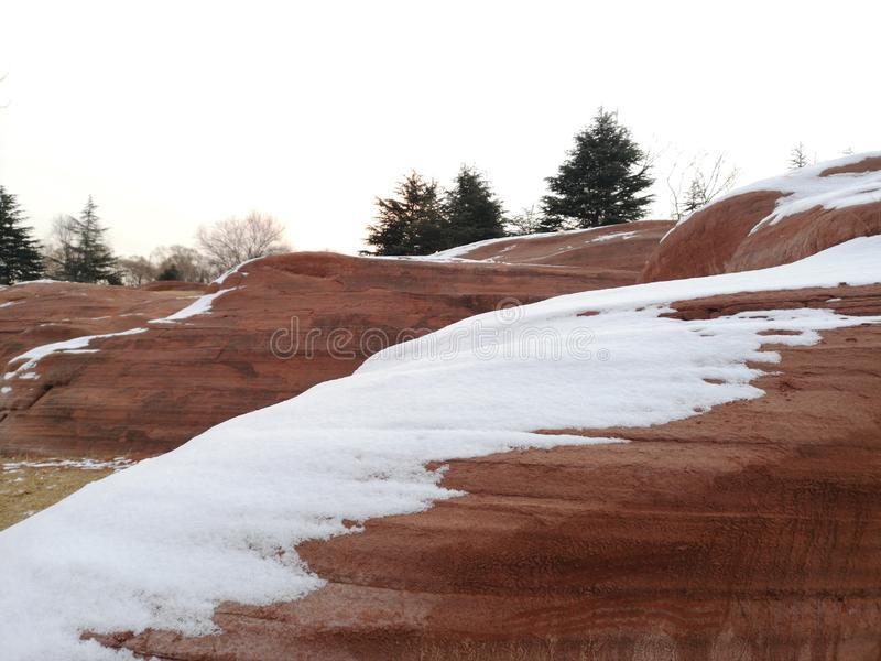 Red stone with white snow in the park stock photo