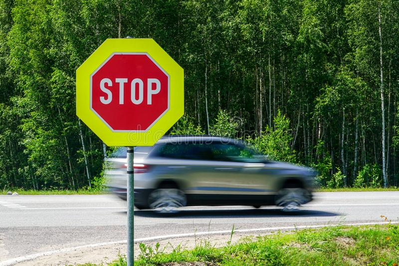Red stop road sign in the foreground and blurred fast car in the background stock photo