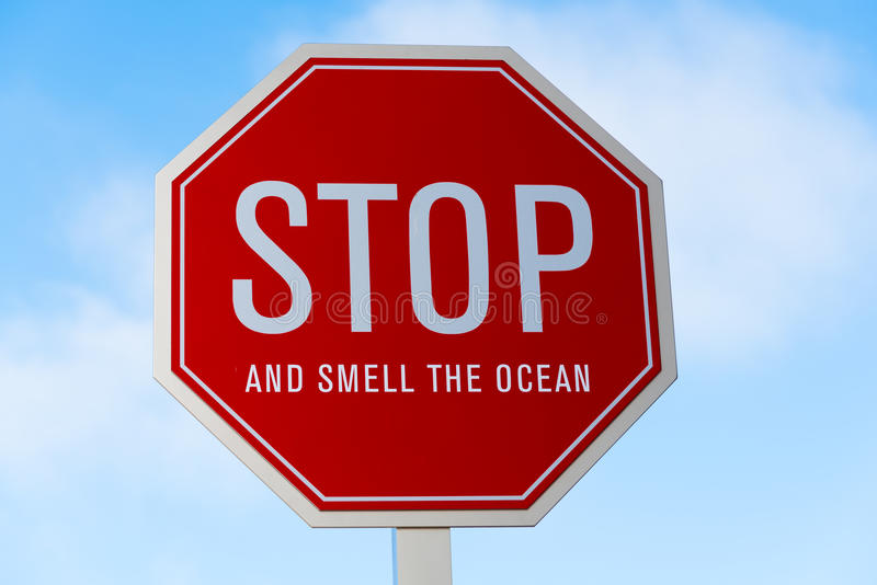 A red stop sign Stop and Smell the Ocean. A stop and smell the ocean traffic, street sign in southern California stock photos