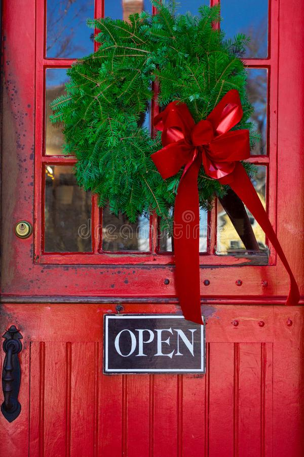 Store entrance door with open sign and Christmas wreath. Red Store entrance door with open sign and Christmas wreath stock photo