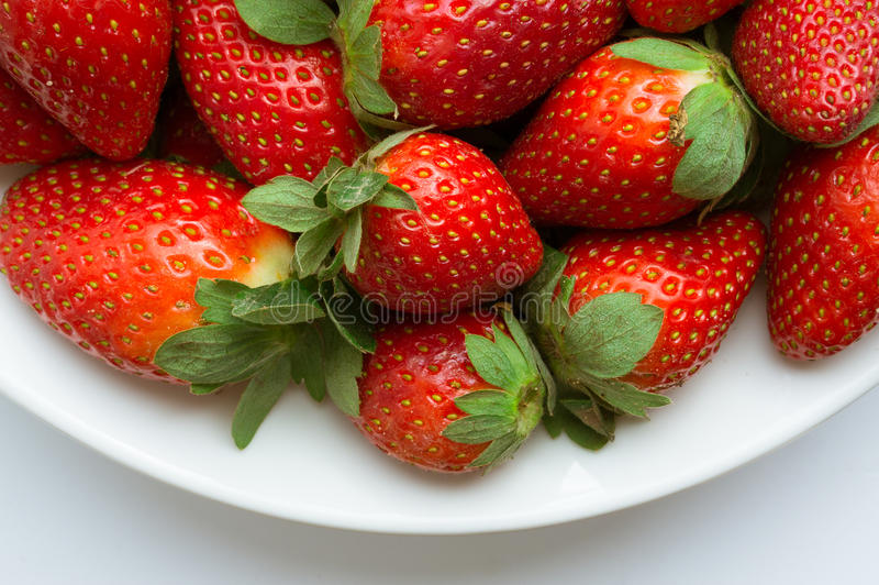 Red strawberries over plate royalty free stock images
