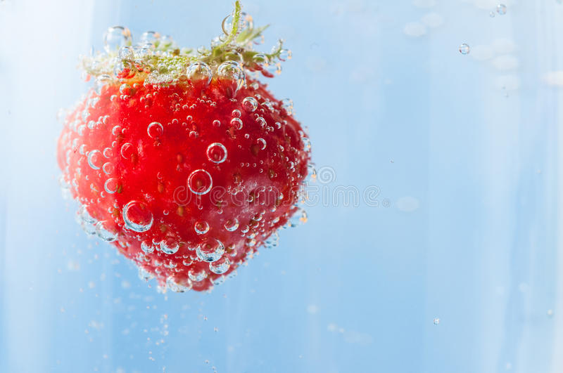Red Strawberry Floating in Bubbles of Sparkling Blue Water stock photo