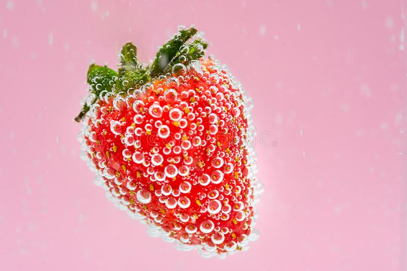 Red strawberry fruit floating in the water on pink background. High value commercial food photography. Fresh beverage in menu. stock photo