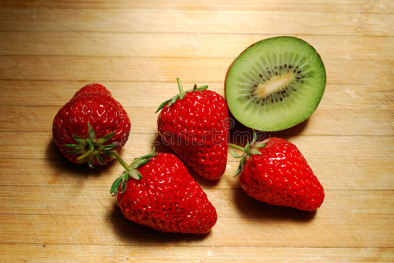 Strawberry And Kiwi On Chopping Board Stock Photos