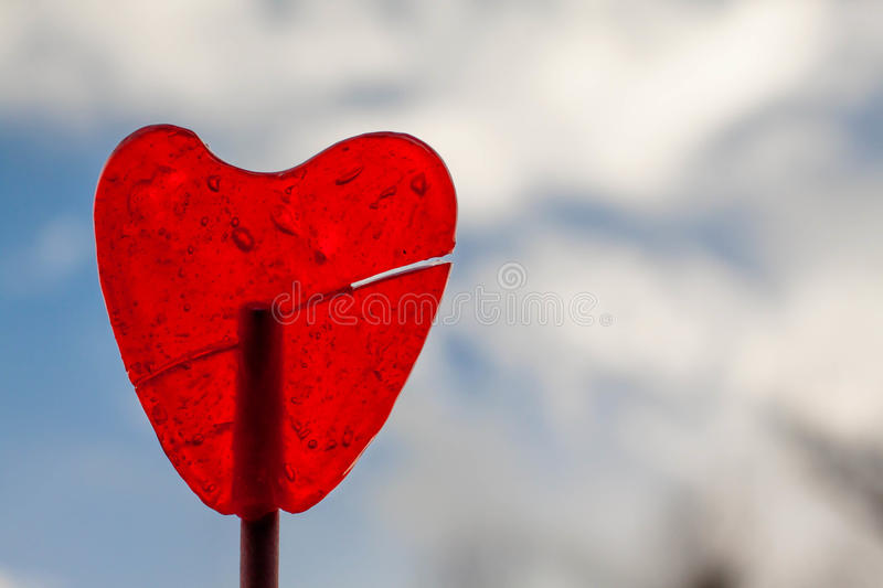 Red strawberry lollipop heart and blue sky royalty free stock photo