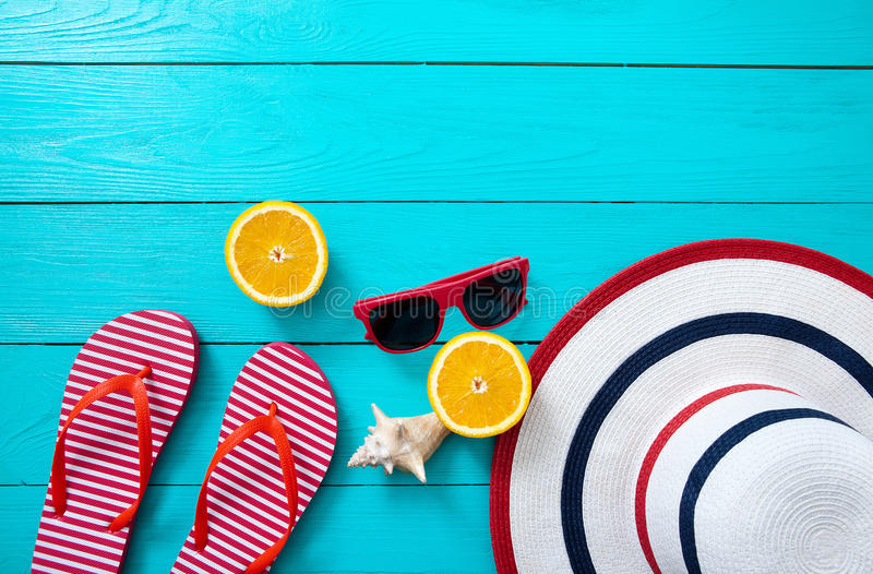 Red striped flip flops, red sunglasses and orange fruit on blue wooden background. Top view and summer time. royalty free stock photography