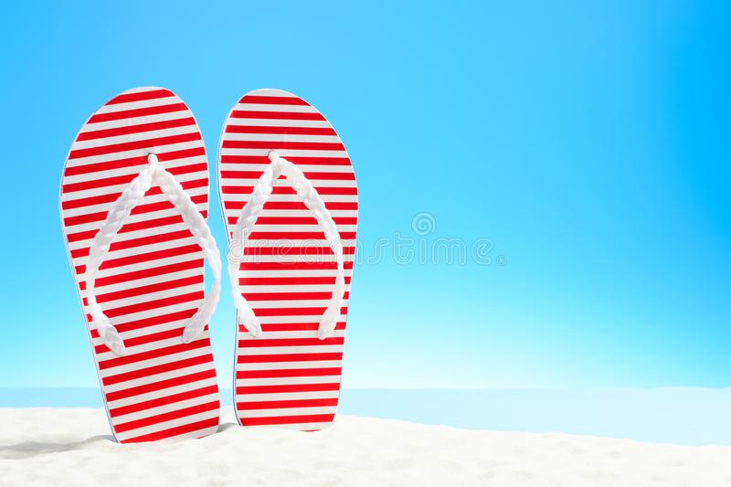 Red striped flip flops on a sandy beach. F royalty free stock photos