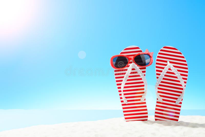 Red striped flip flops and sunglasses on sandy beach. F stock photos