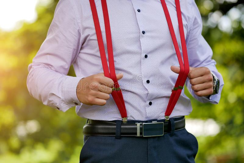 Red stylish men`s suspenders on blue shirt background royalty free stock photo