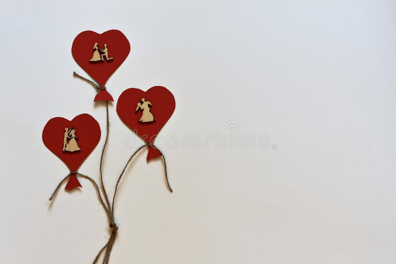 Red stylized balloons in form of hearts with vintage dancing wooden figures of lovers on white background. Minimalism style royalty free stock image