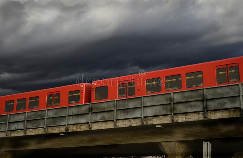 Red subway cars on a concrete overpass against a dramatic sky royalty free stock photo