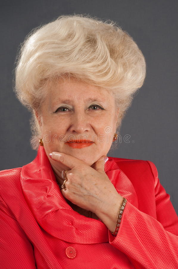 Red suit of the elderly lady. stock photos