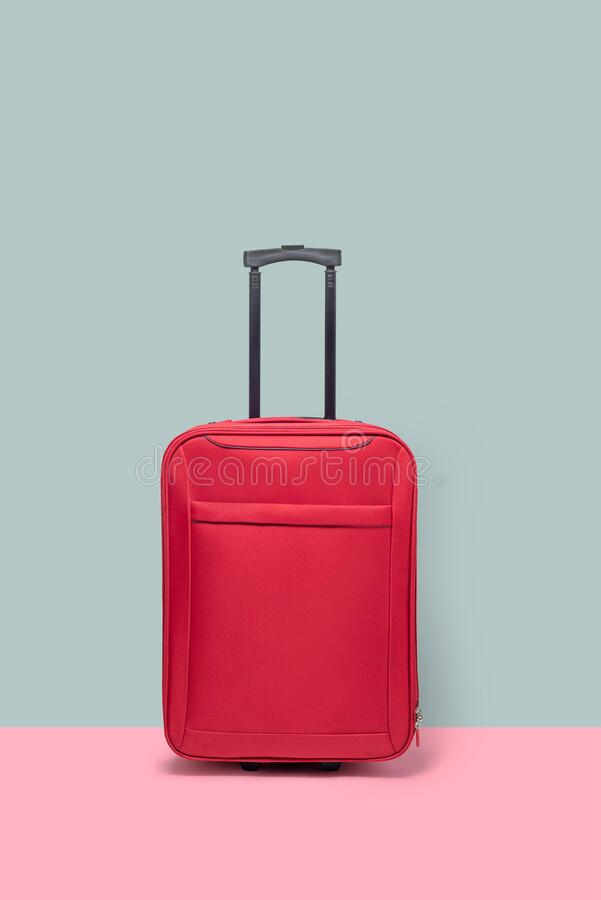 Red suitcase, standing next to a colored wall and floor. no people royalty free stock images