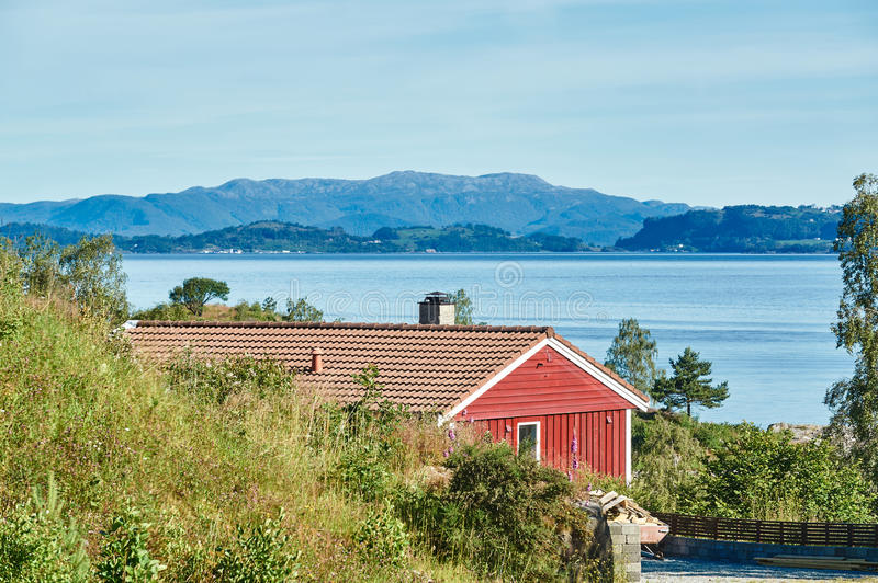 Red summer cottage among the rocks, fjord stock photo