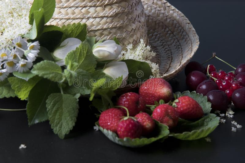 Summer fruits straw hat. Red summer fruits with some flowers and a stock photos