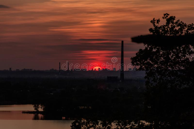 Red sun has set over the silhouettes of the city stock image