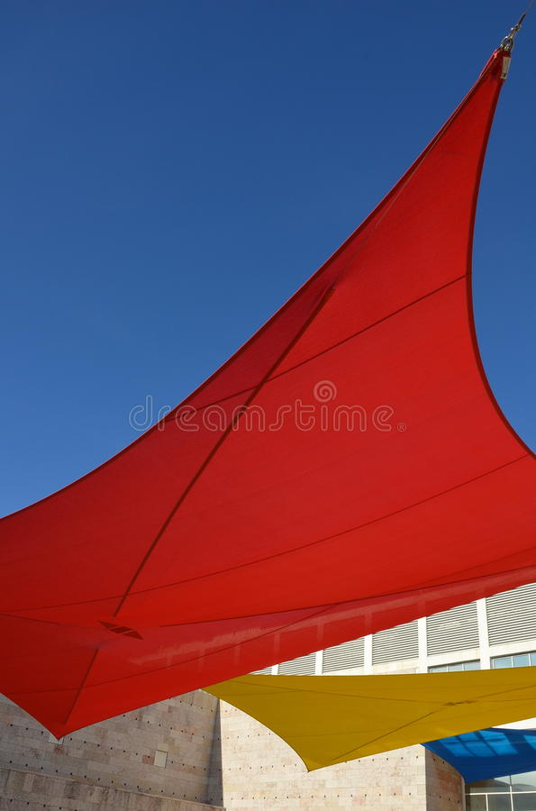 Red sun shade. A red sun shade is seen against the blue sky with a yellow and blue sun shade in the back stock images
