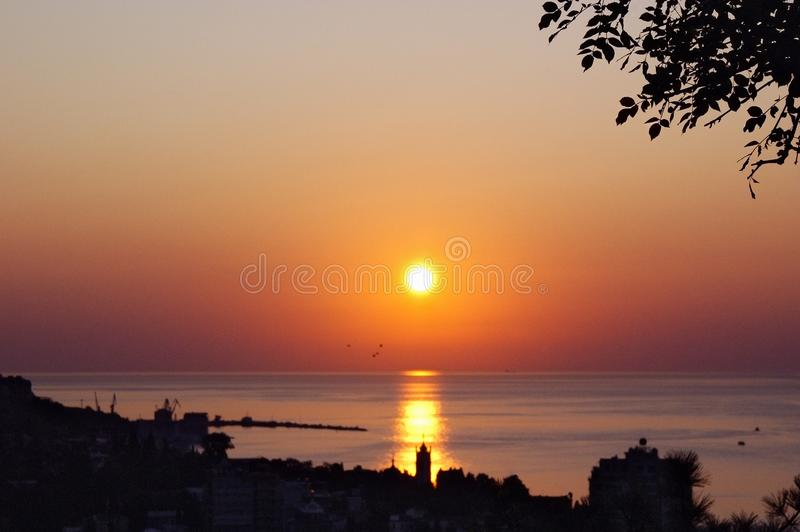 Red sunrise at sea coast with sun in sky stock photo