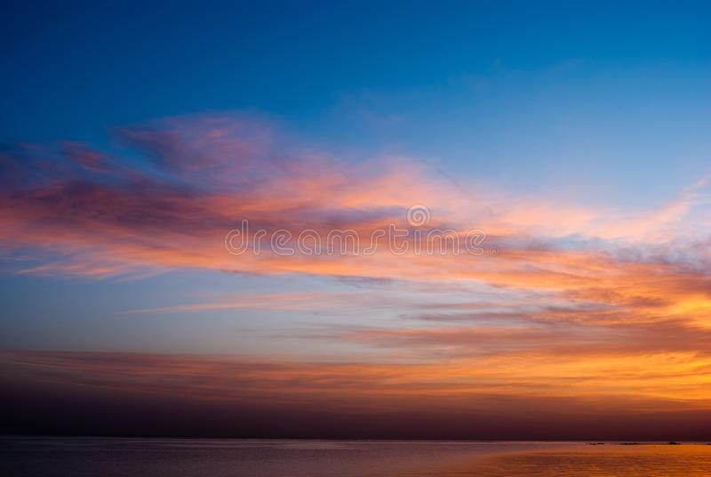 Red sunrise in blue sky above ocean. Morning early blue sky with clouds morning on sea. Sunrise on blue sky and cold water. royalty free stock photography