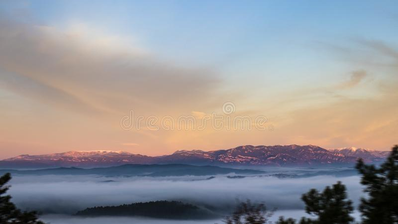 Red sunrise mountain landscape over foggy clouds and blue sky royalty free stock photos