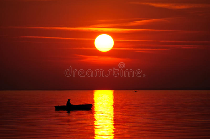 Red sunset. Over the lake, with boat royalty free stock photo