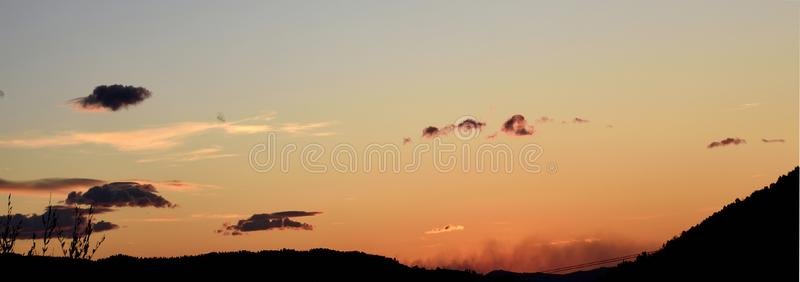 The red of the sunset among the black clouds. Red sunset in the hills. dark clouds alternate with light cloudsn royalty free stock images