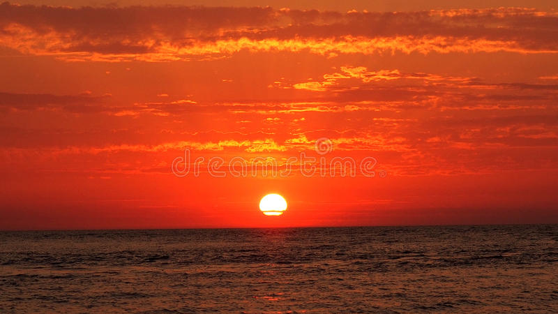 Sunset dark red clouds over sea. Red sunset, sun and clouds over sea royalty free stock images