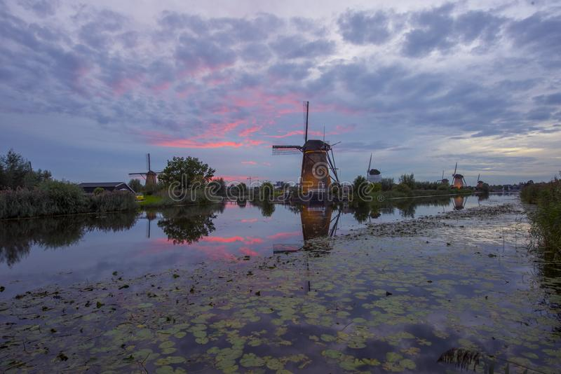 Red sunset at kinderdijk windmills in holland stock photo