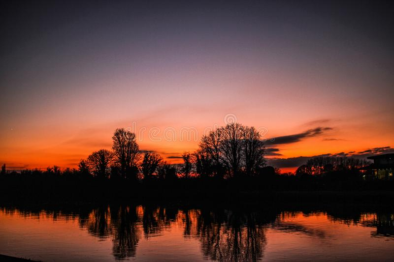 Red Sunset near Kingston upon Thames in England in December. Trees in silhouette reflected in the River Thames. A vignetted clear winter sky stock photography