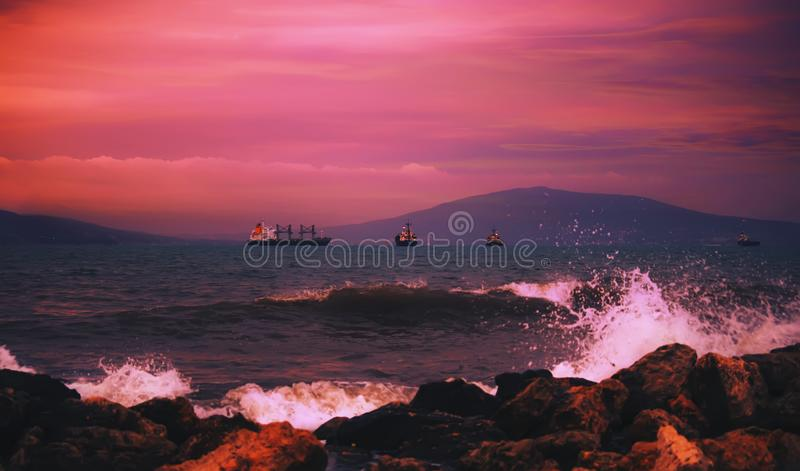Red sunset over the black sea, mountains, purple sky. Summer sea scenic landscape in stormy evening royalty free stock photo