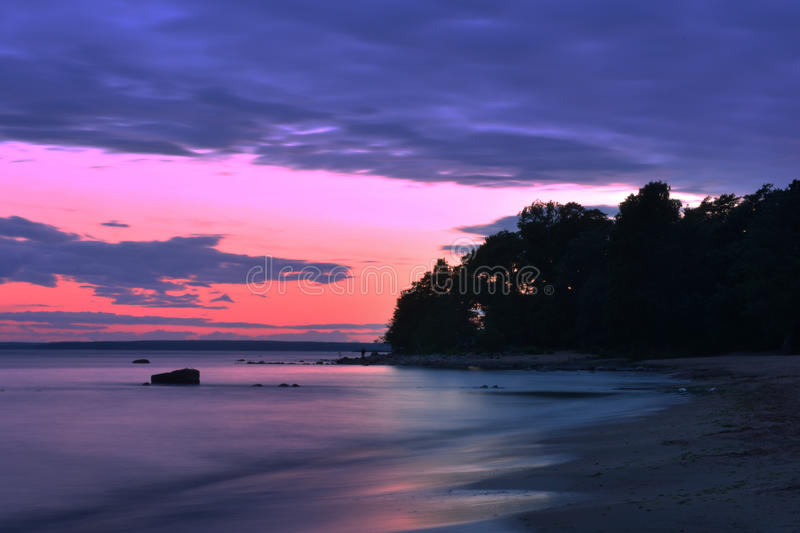 Red sunset over the coast and the sea pink. stock photo