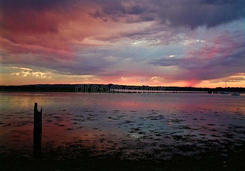 Red sunset with rain clouds over water and land in the distance. Red sunset with rain clouds and land in the distance stock photos