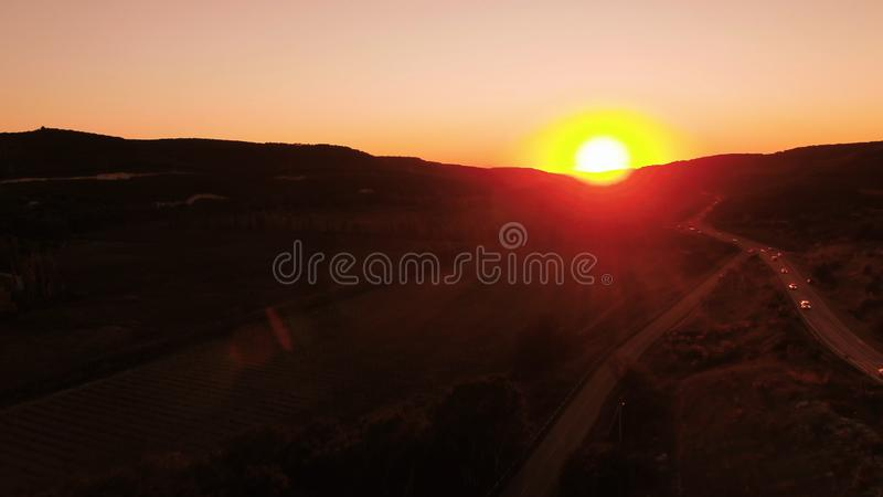 Red sunset. Shot. Red sunset sky with bright disk of sun partially hidden by mountains. Top view of traffic on rural. Red sunset. Red sunset sky with bright disk stock photography