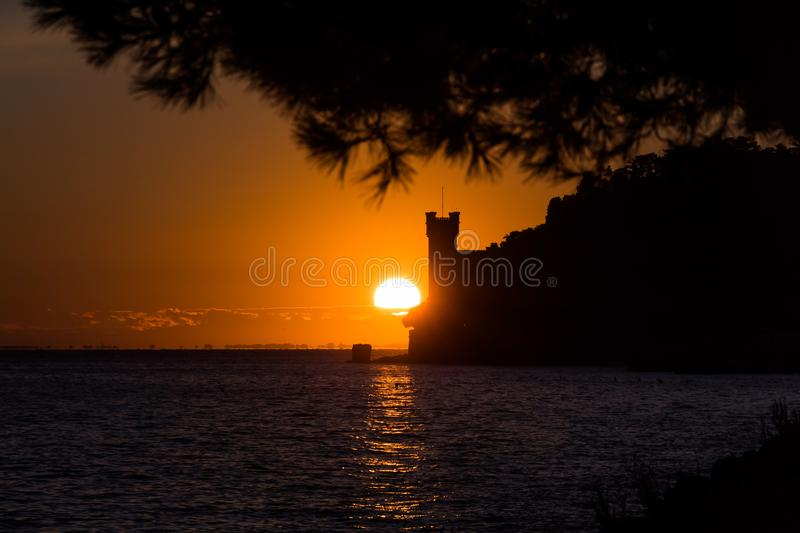 A red sunset on the sea with a gold sun disk and a black castle royalty free stock images